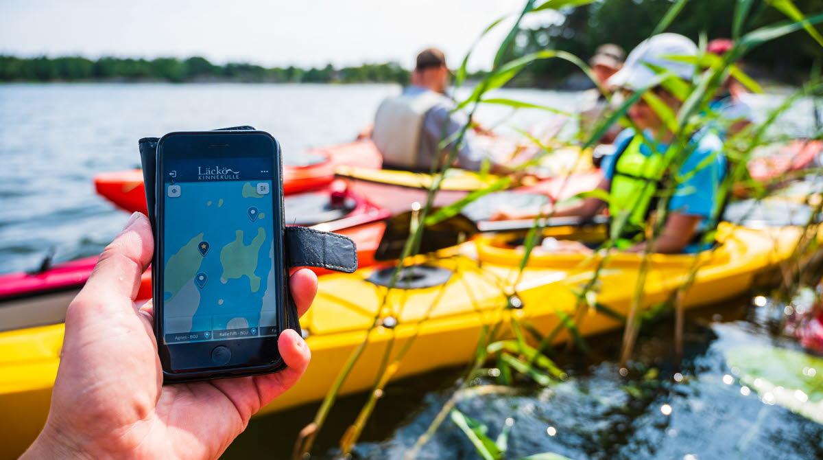 En hand som håller i en mobil. i Bakgrunden syns några personer som sitter i kajaker på vattnet.