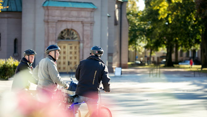 Tre män på cyklar med står utanför en kyrka och pratar.