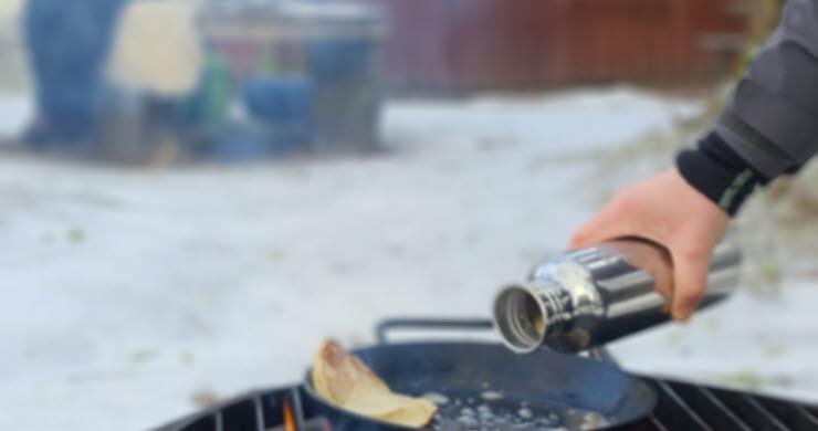 Matlagning över eldstad utomhus.