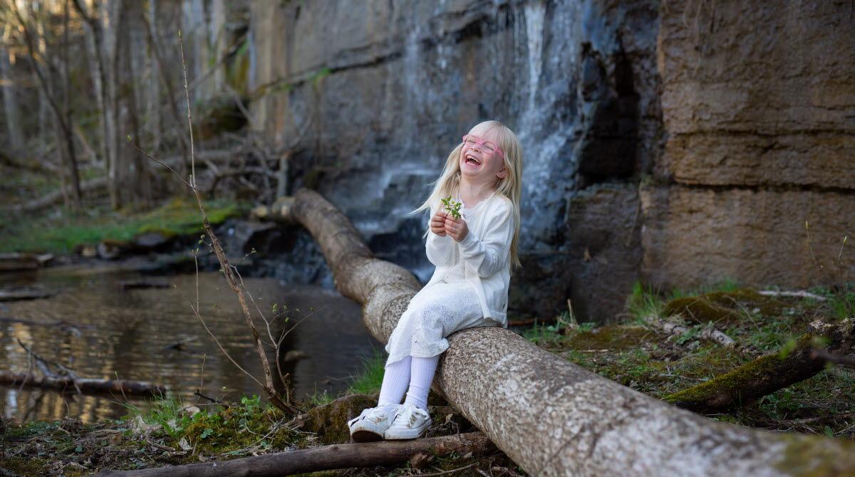 Flicka som sitter vid ett vattenfall.