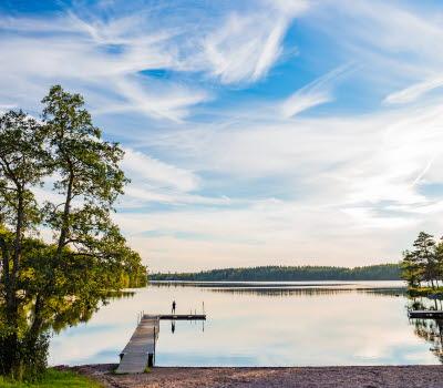 Utsikt över en brygga och en sjö med lätta moln och blå himmel.