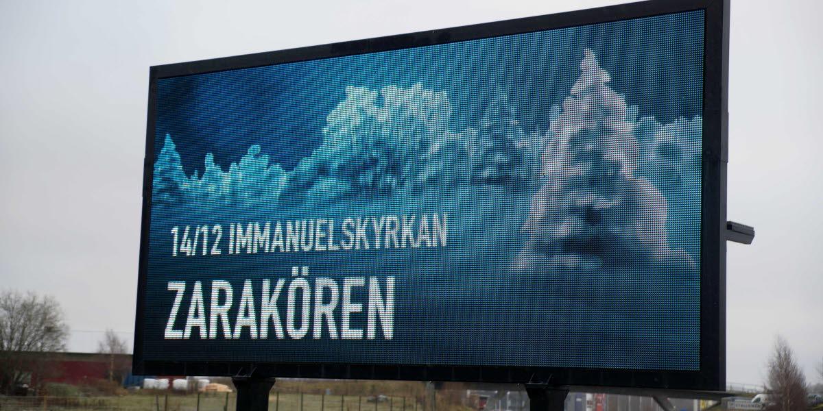 Stor digital skylt som står intill vägen visar reklam för Zarakörens konsert, mot en vintrigt landskap.