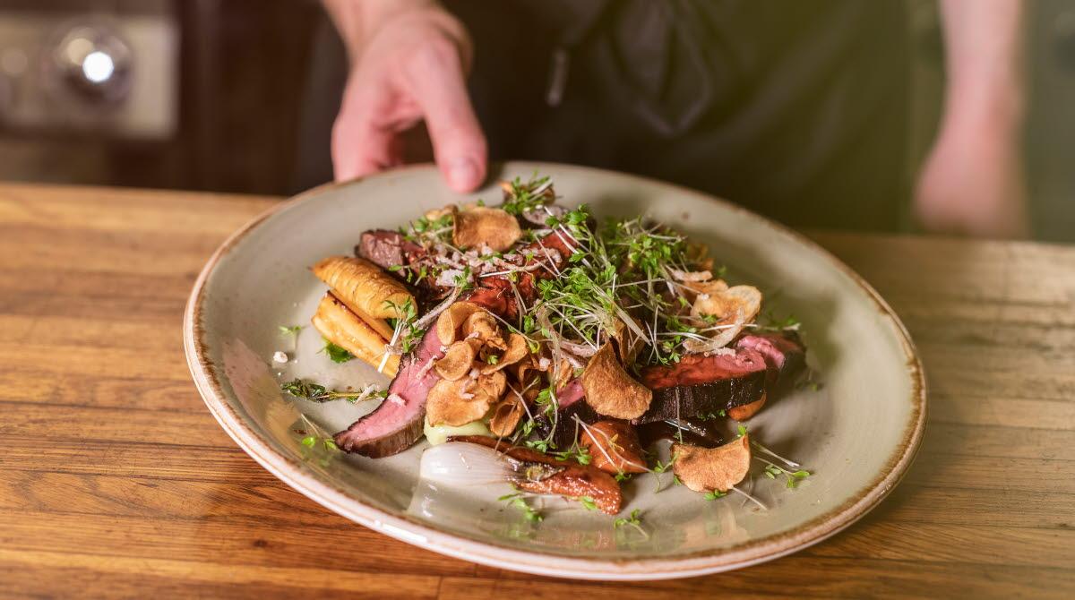 En hand som håller upp en tallrik med kött och grönsaker.