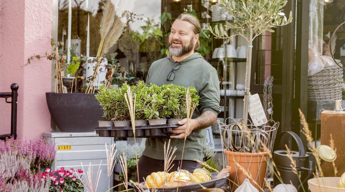Man som bär på en bricka med massa växter utanför en blomsterbutik.