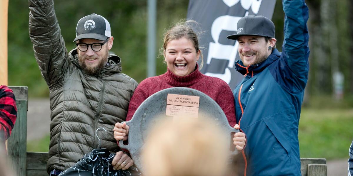Vinnaren av SM i utomhusmatlagning 2019. Lag Skärselden från Falkenberg. En ung, glad tjej och två unga glada killar står på prispallen. Tjejen håller i vandringspriset och killarna sträcker upp armarna med knutna nävar som riktiga vinnare.