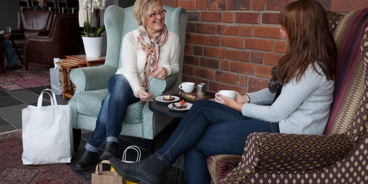 Två kvinnor sitter i varsin fåtölj och fikar.