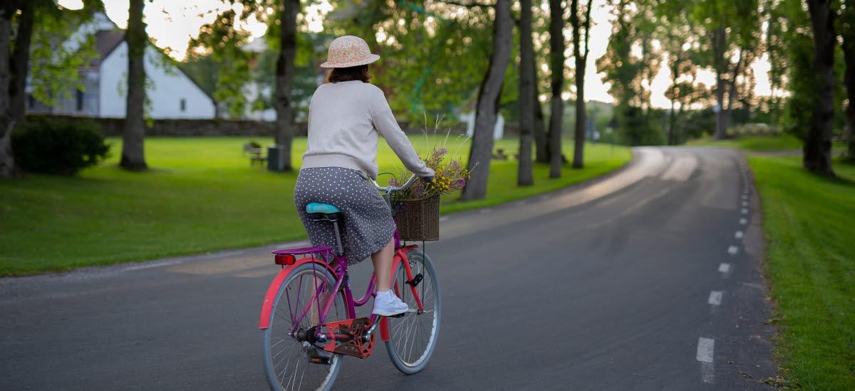 En kvinna på cykel på landsväg.