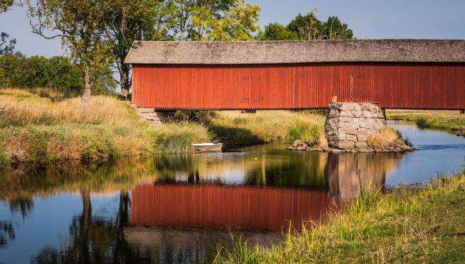 En långsmal bro som är inbyggd i falurött trä och har ett grått tak går över ett stilla vattendrag. Bron speglas av i vattnet.
