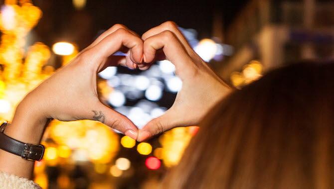 Två händer format ett hjärta. I bakgrunden ser man juleljus.