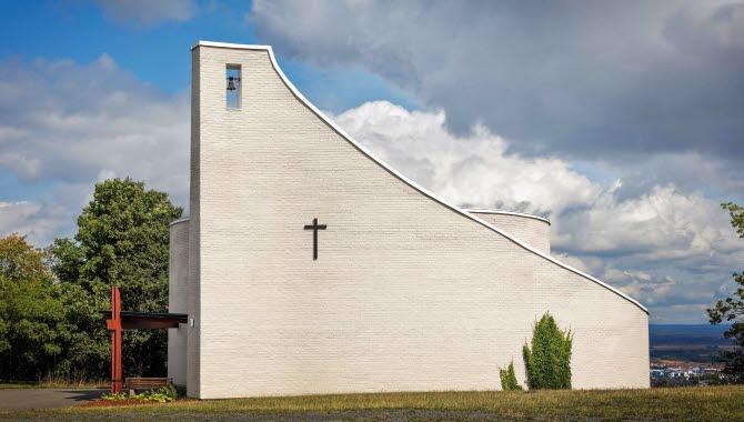 En vit modern stenkyrka. I bakgrunden ser man en milsvid utsikt över Skövde. Himlen är bitvis blå med dramatiska gråa moln. På kyrkan sitter ett litet svart kors.