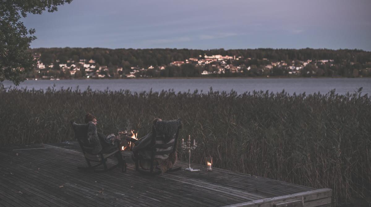 Två personer sitter i gungstolar vid sjön och tittar in över Ulricehamn