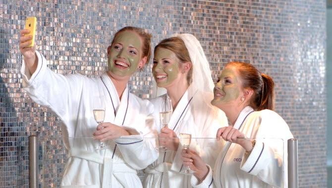 Tre tjejer poserar glatt för ett kort inne på spa-avdelningen på Strömstad Spa. De har gröna ansiktsmasker, är iförda badrockar och håller varsitt champagneglas.