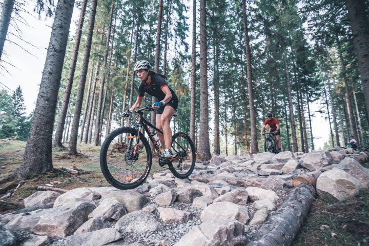 Tjej på cykel åker över ett stenmurshinder