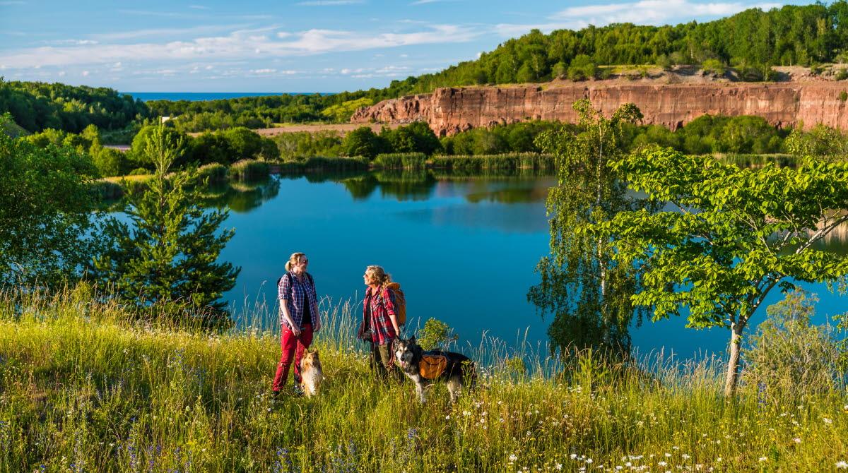 Två personer står vid kanten av ett vattenfyllt stenbrott med sina hundar.