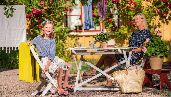 Mamma och dotter som sitter i Forsbergsgården trädgård i Hjo, ett privatboende mitt i de gamla stadsdelarna.