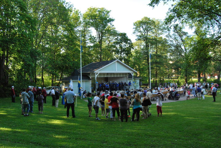 Människor som ser på ett uppträde i Bruksvilleparken i Tidaholm.