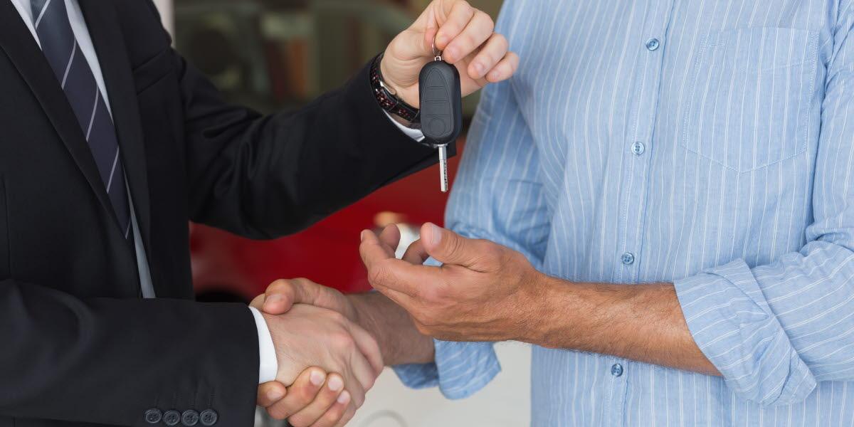 En bilförsäljare som lämnar över en bilnyckel till en köpare.
