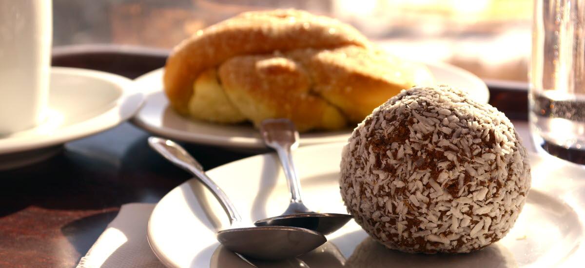 En kaffekopp med bulle och en chokladboll på ett fat med två skedar