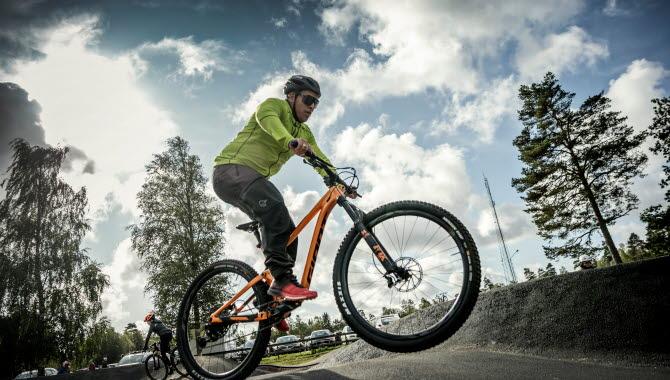 Kille i neonfärgad tröja och svarta byxor hoppar fram med sin orange mountainbike på den asfalterade pumptrackbanan.