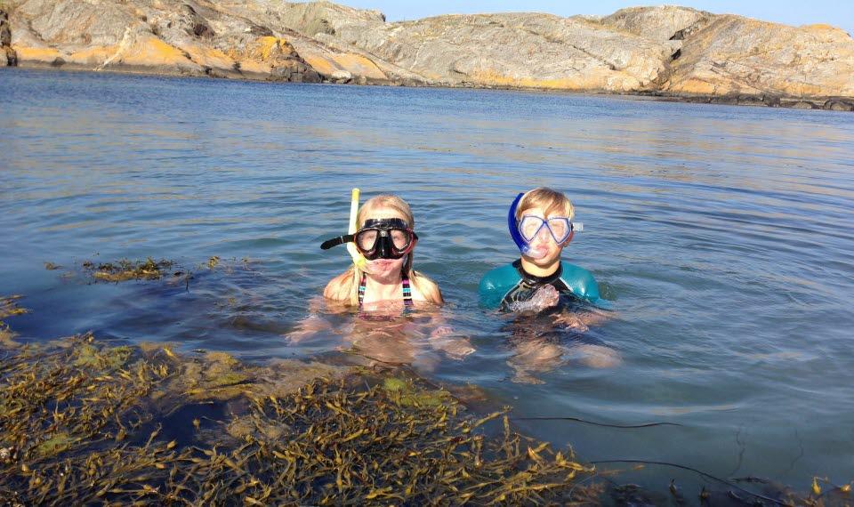 Två barn badar i havet och har snorkel på sig.