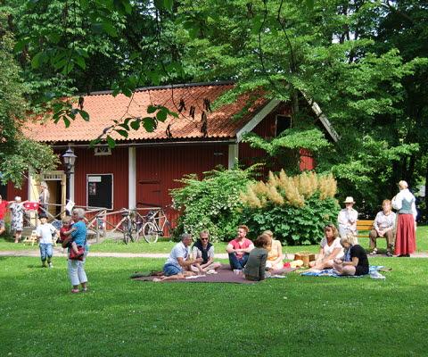 Personer som sitter i gröngräset och fikar och personer som går på Turbinhusön, som är en park med vackra gamla hus i Tidaholm.