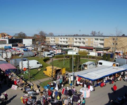 En vy över en marknad med med människor som handlar i en liten stad.