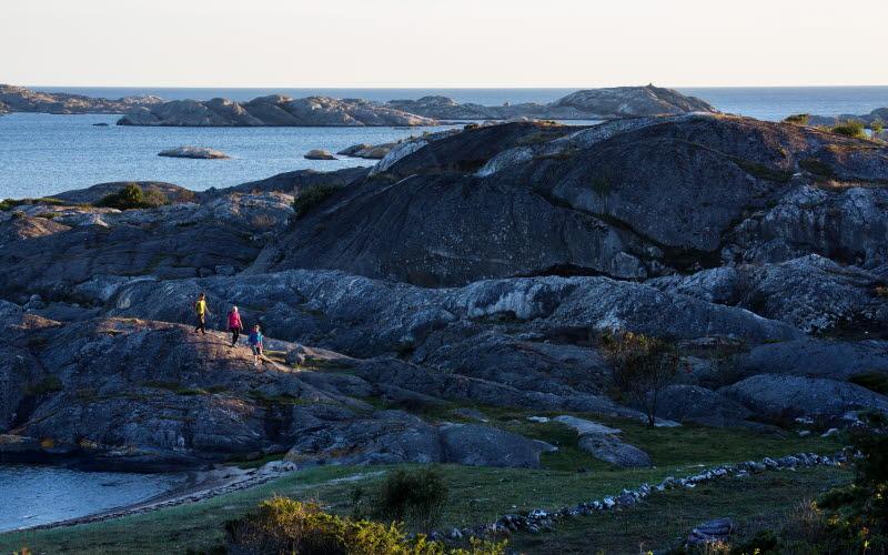 Tre personer vandrar längst en klipphäll på Nordkoster.