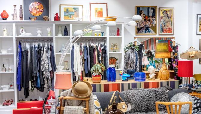 Butiksbild tagen i en second hand-butik. På bilden finns äldre möbler, en designlampa och vintagekläder.