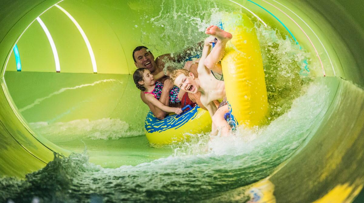 Två barn och en man åker tillsammans på badringar i en vattenrutschkana.
