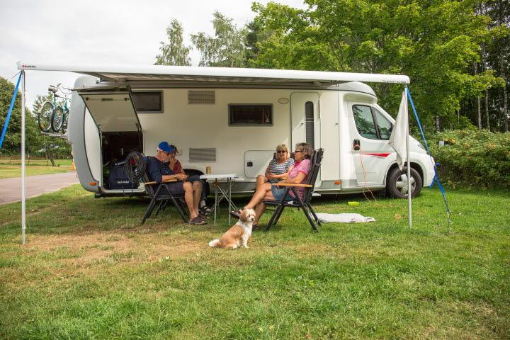 Personer som sitter framför en husvagn på Tidaholms Camping.
