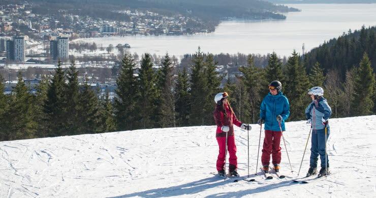 Tre barn i färgglada kläder på skidor på toppen av Ulricehamn Ski Center.