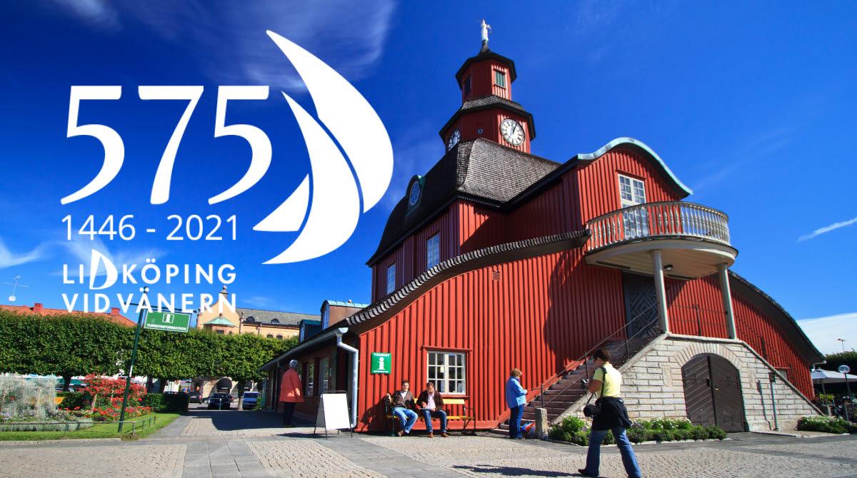En röd träbyggnad med blå himmel bakom. Det är vit text i bilden där det står: 575 år 1446-2021, Lidköping vid Vänern.