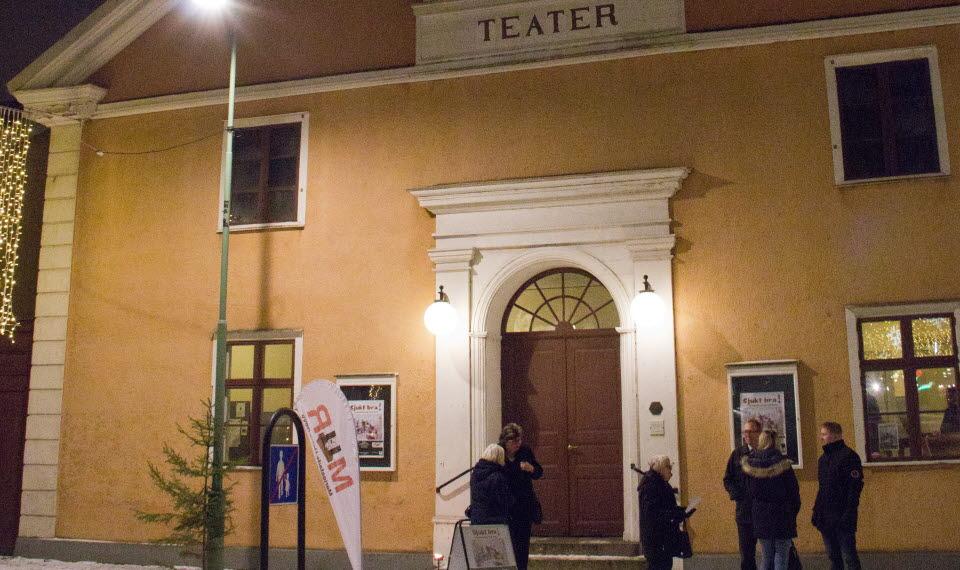 Sex personer väntar utanför entrén till Mariestads teater, en vinterkväll.