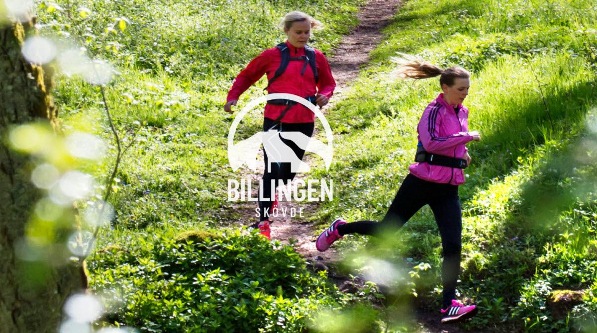 Två kvinnor är ute och springer på en stig i en grönskande skog iklädda mörka byxor och rosa och röd tröja.