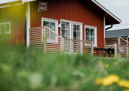 Röd stuga med en altan framför.
