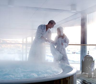 Två personer står vid Strömstad Spas utomhus-jacuzzi, iförda badrockar. Det är en vinterdag och ånga stiger ifrån jacuzzins varma, bubblande vatten.