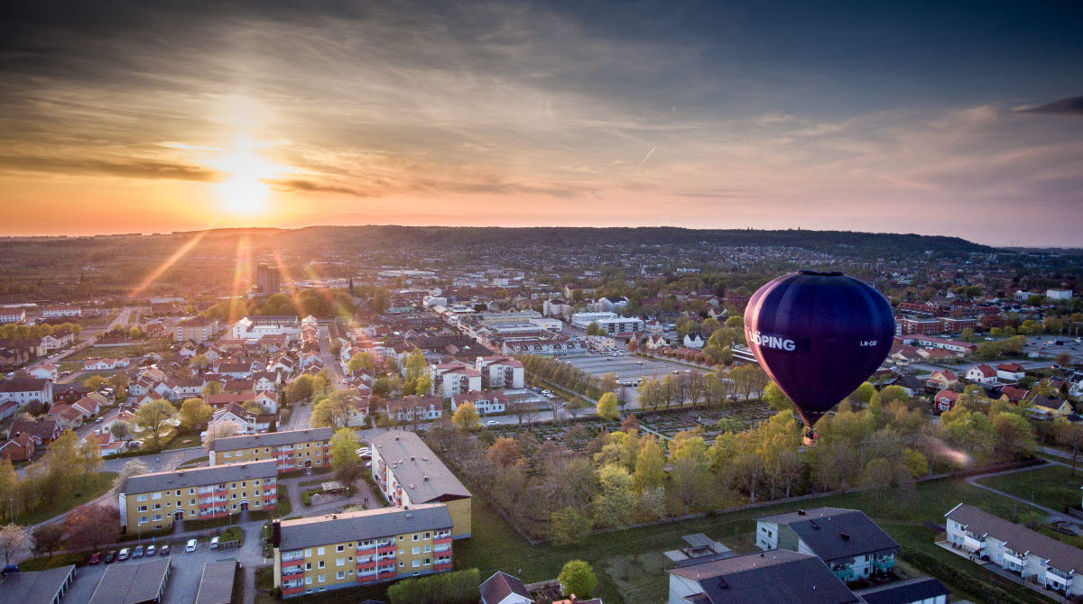 A black hot air balloon with the text Falköping on flying over the city.