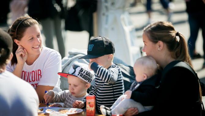 Två kvinnor och tre barn sitter och äter och pratar vid ett bord på en festival.