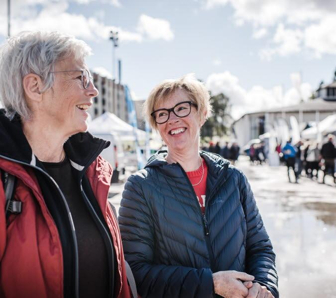 Två kvinnor står i strålande solsken på mässa och pratar
