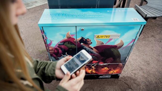 En person med en smartphone i handen står framför ett elskåp inklätt i dataspelskonst.