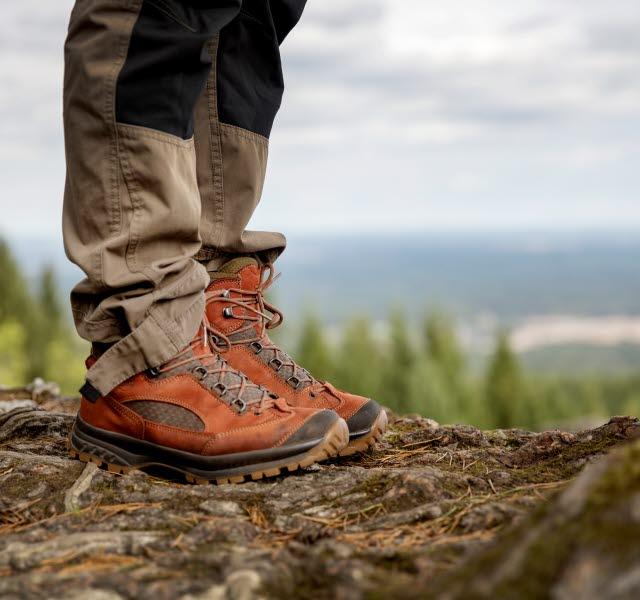 I bild syns en persons byxor och vandringskängor. Personen står på en höjd med en utsikt i bakgrunden.