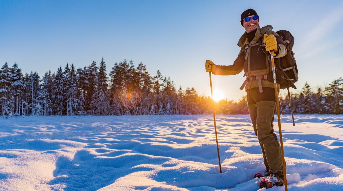 Soligt vinterlandskap där en person står i snön med skidor på fötterna och stavar i händerna.