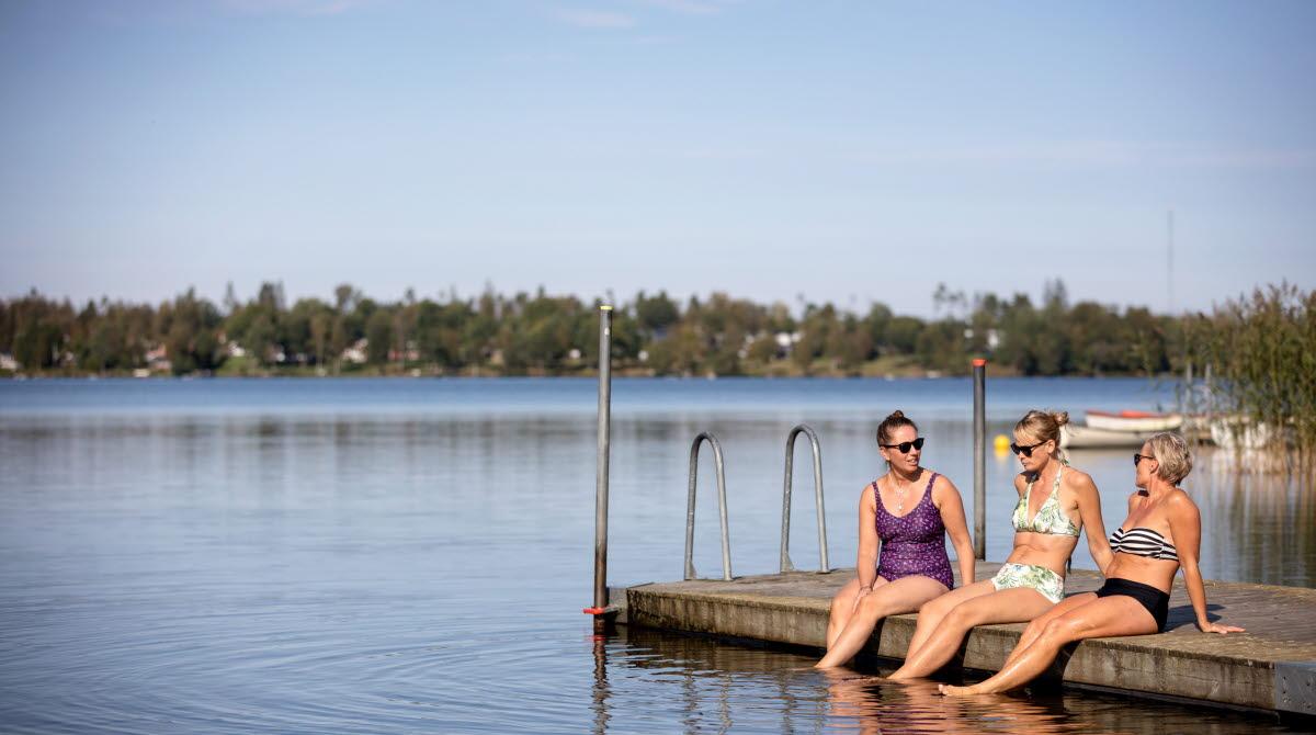 Tre kvinnor sitter på en brygga med fötterna i vattnet