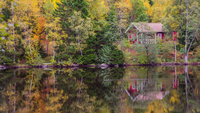 En röd stuga som speglar sig i en blank sjö. Den omgärdas av gula och gröna höstträd.