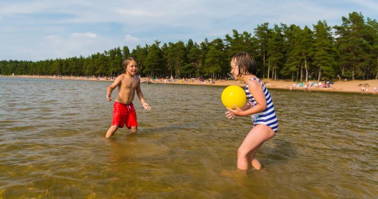 En pojke och en flicka kastar boll till varandra i vattnet.