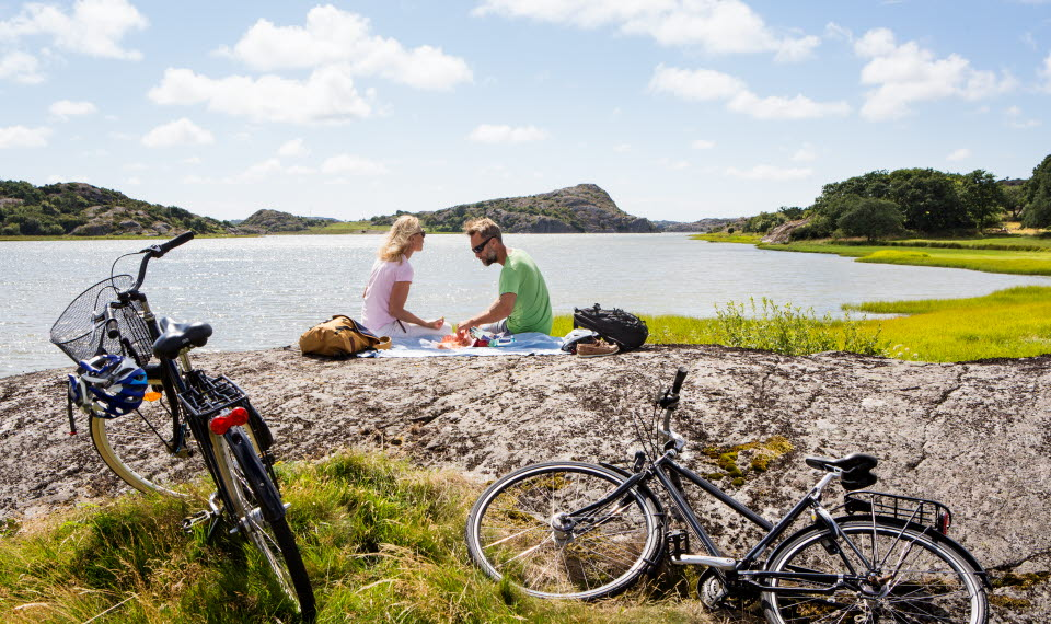 Couple sitting on a cliff by the ocean, two bikes is nearby