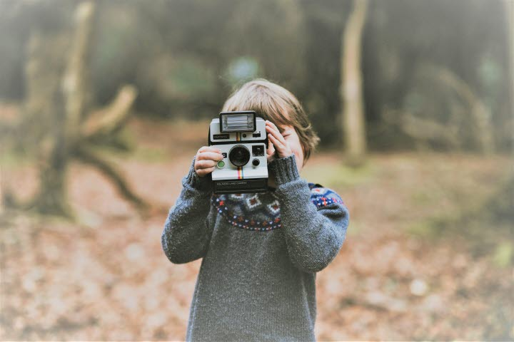 A kid in the forest with a camera.