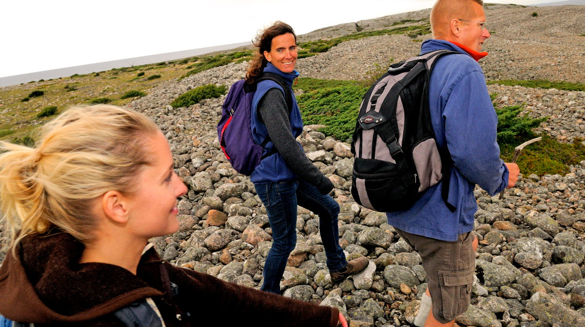 Three people are hiking across a field of cobblestone at the Koster islands.
