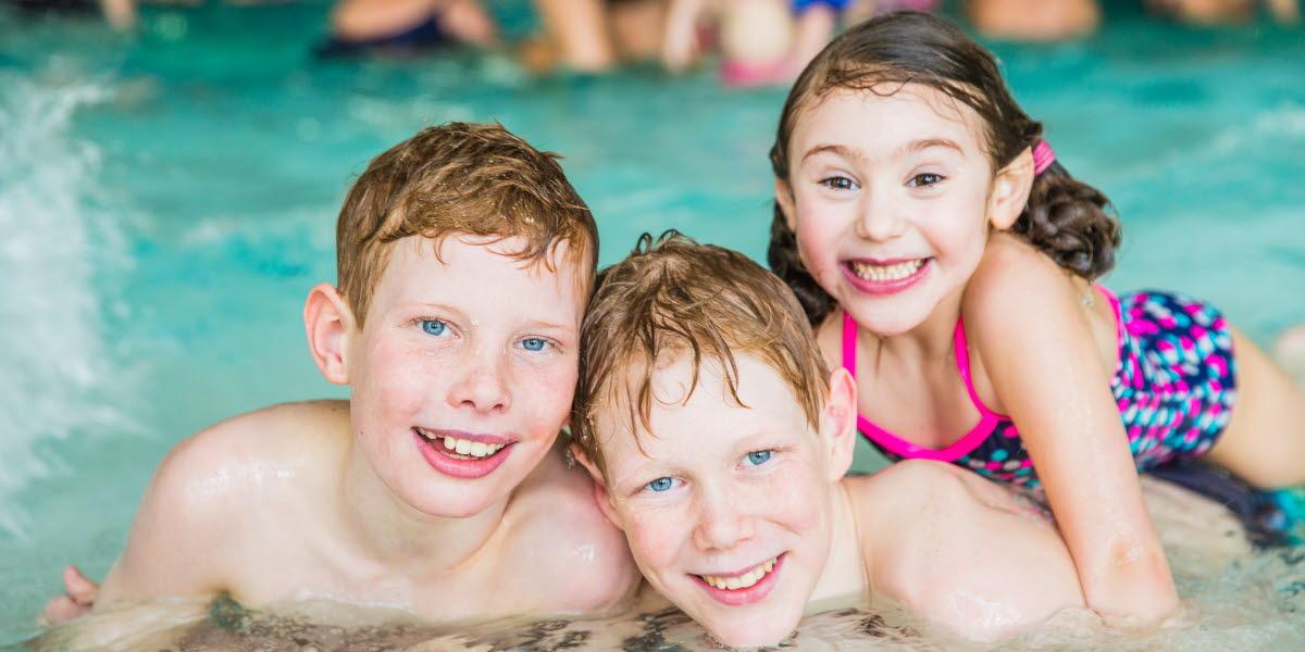 Tre barn ligger i vattenbrynet och skiner upp framför kameran inne på Arena Skövde
