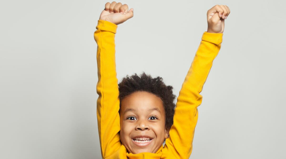 Glad pojke i gul tröja ler brett och sträcker upp sina armar i luften.